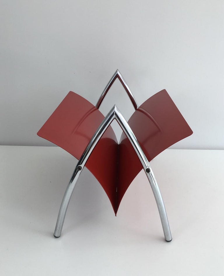 This magazine rack is made of a chrome base on which stands a red lacquered metal piece receiving the magazines. This is a French design, circa 1970.