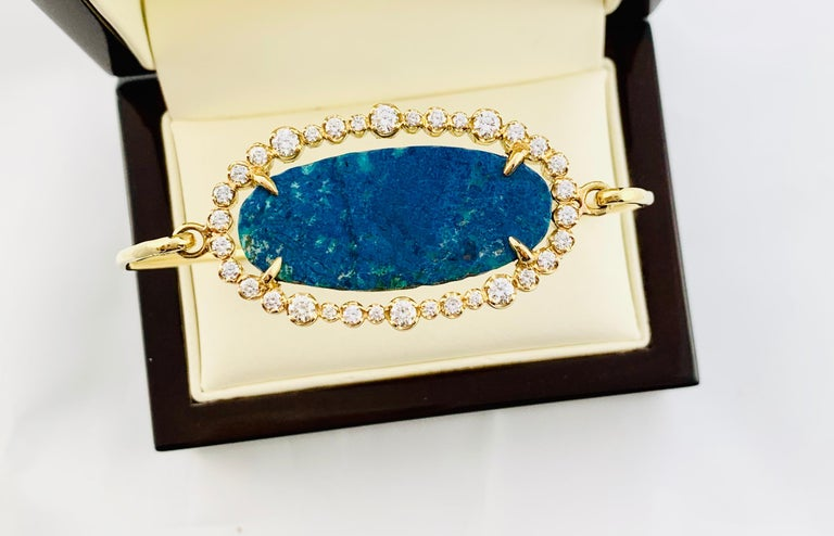 Gorgeous 18K yellow Gold Designer Bangle Bracelet. This beautiful piece features a 12.50 Carat Oval Azurite Center Stone that is surrounded by 34 Brilliant Diamonds. The diamonds are H-I in color and VS2 Clarity. the diamonds  have an estimated