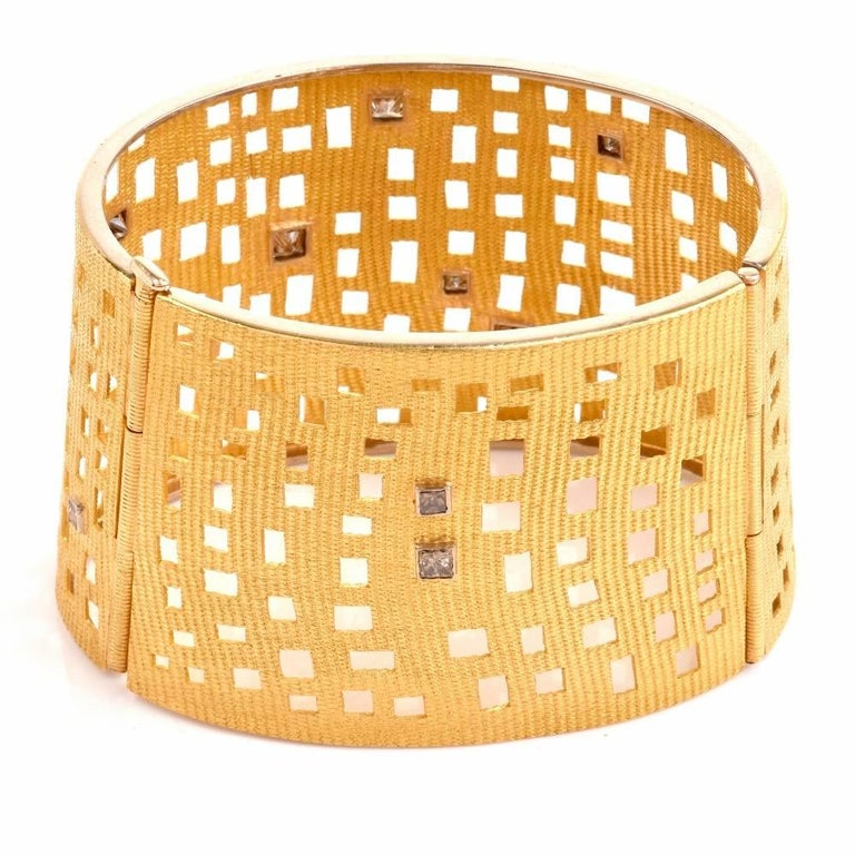 This aesthetically fascinating wide bracelet is rendered in 18 karat matted and finely textured yellow gold, weighing 73.9 grams and measuring 7 inches around the wrist and 1.75 inches wide. Enriched with ornate asymmetric perforations, the bracelet