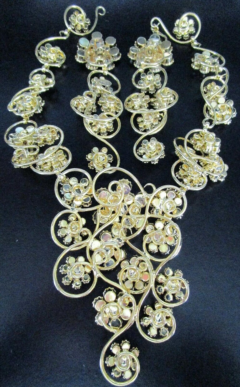 Vintage Designer Marie Ferra Signed Necklace and matching Clip-on Earrings. Golden scroll design with Hand set Sparkling Ice Crystal Rhinestone Flowers. Signed: MARIA FERRA. Necklace measures approx. 17