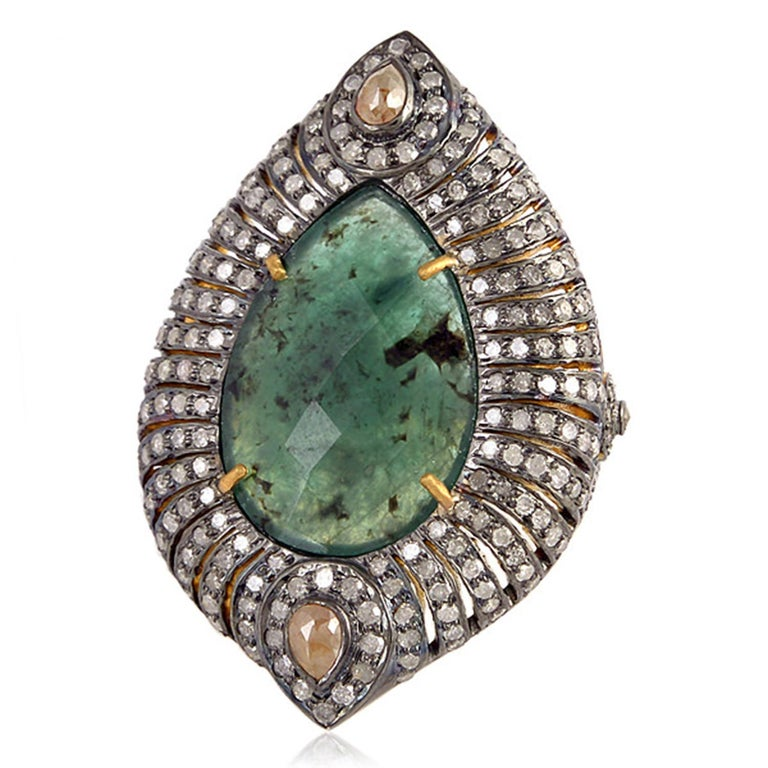 Designer emerald ring with diamonds around is a great cocktail ring with slice pear shape emerald in center.   Rings Size: 7.25 ( can be sized for a cost )  18kt: 3.158gms Diamond: 2.76cts Silver: 9.02gms Emerald: 6.4cts