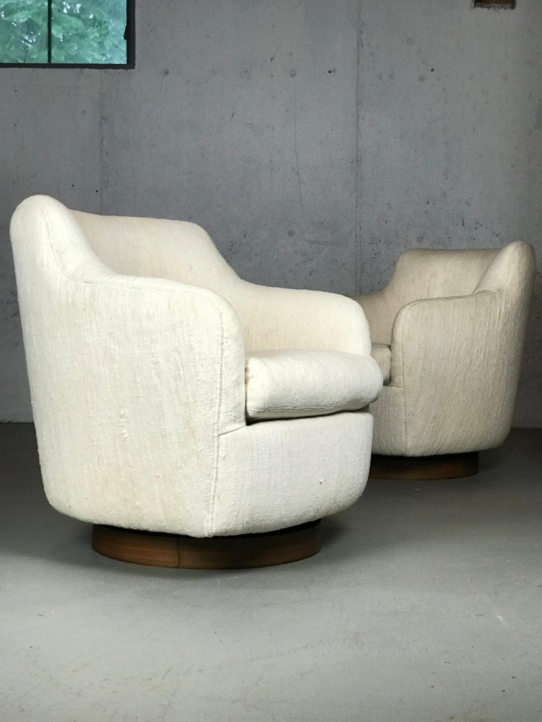 Lovely pair of lounge chairs designed by Milo Baughman for Thayer Coggin. Original nubby cream upholstery is in nice condition. Some stains under the seat cushion (not showing). Walnut bases.