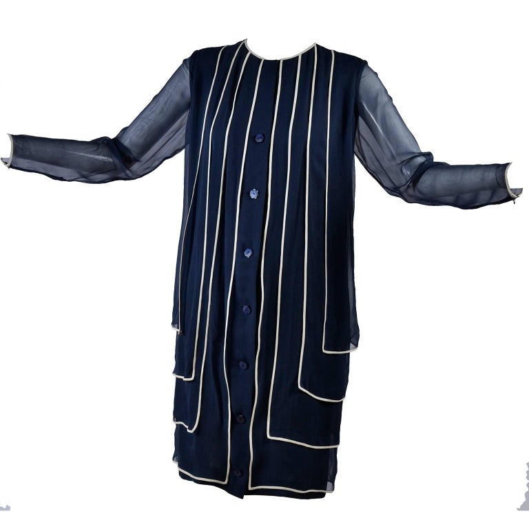 This is a lovely assumed couture vintage dress in navy blue silk chiffon with white trim.  The dress has 4 layers over a solid blue underdress and the sleeves zip at the cuffs and appear to effortlessly fit into the design as if they are one of the