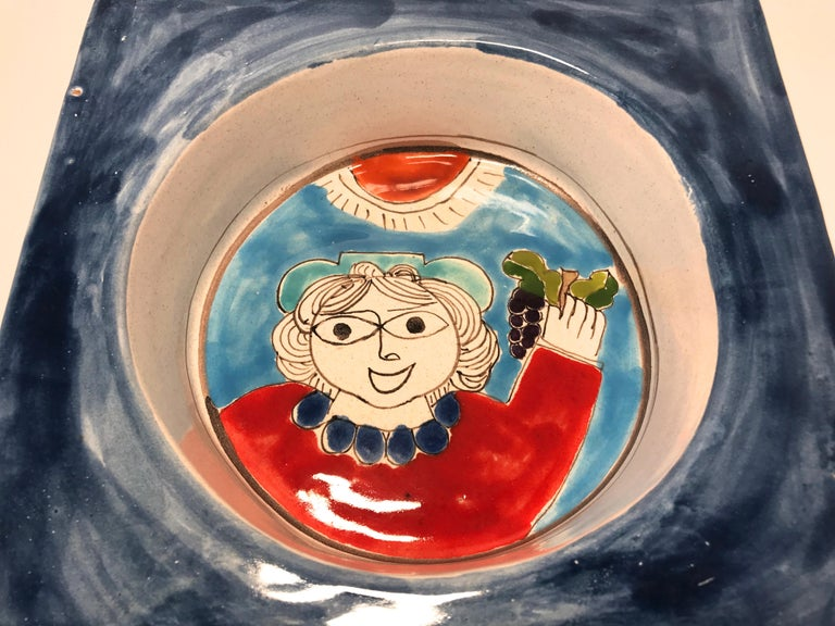 DeSimone of Italy, 'Happy Grape Lady' is typical of DeSimone's colorful and playful art. This bowl is weighty, deep and square - a most unusual piece for the DeSimone collector  circa 1960s Signed DeSimone, Italy 102 on reverse Measures: Height