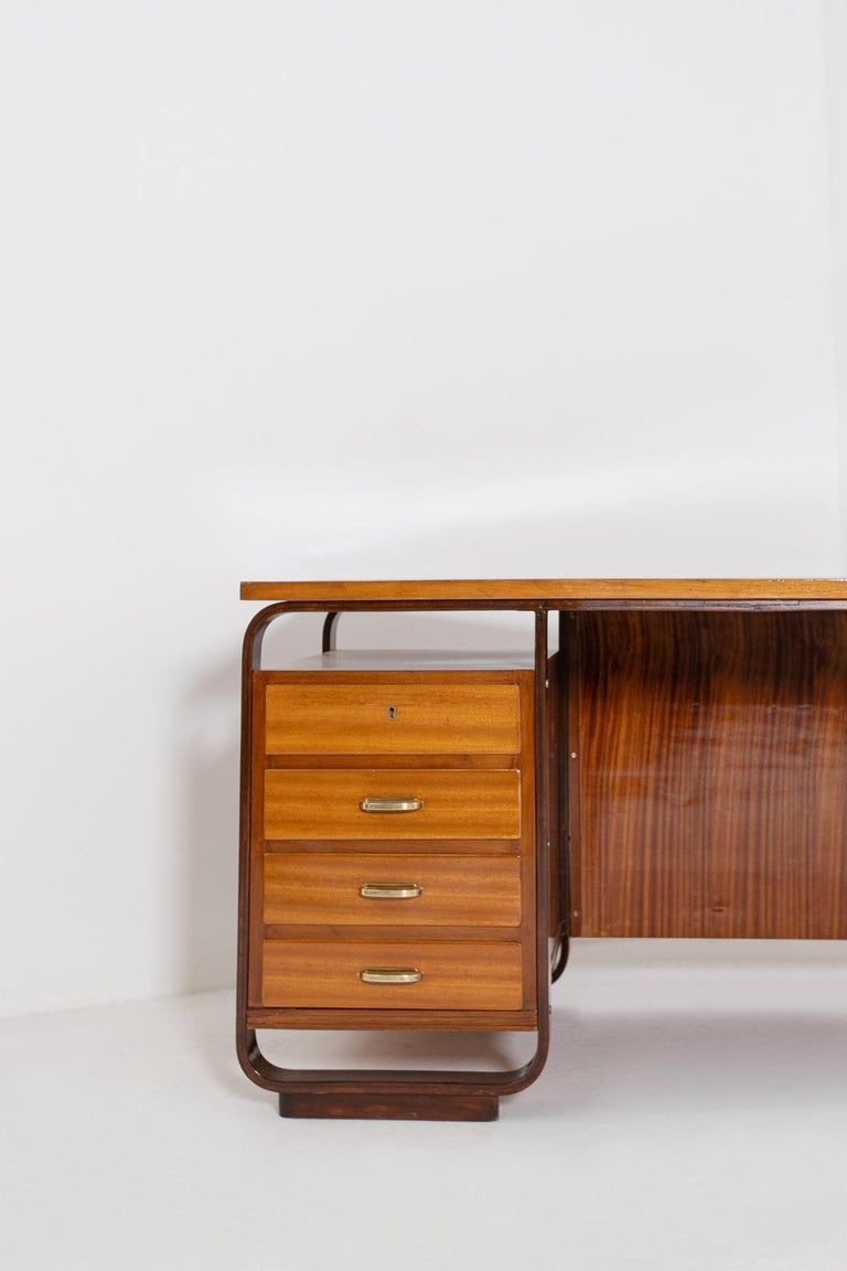 Imposing desk by Giuseppe Pagano, 1940. Scrivania designed for the Bocconi University in Milan Wood. Execution Maggioni, Varedo, ca. 1940. We notice two types of essences for its realization. The peculiarity of the desk are its side drawers framed