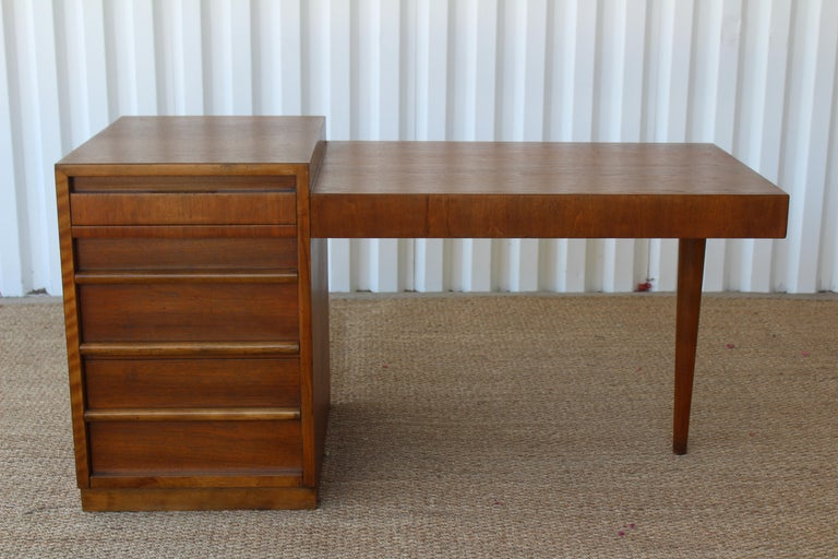 Mid-Century Modern walnut desk designed by Robsjohn Gibbings for Widdicomb, U.S.A, 1950s. Features 4 drawers and a pullout / pull-out board for extra workspace. The drawers feature oak interior dividers for filing paper and storing accessories. This