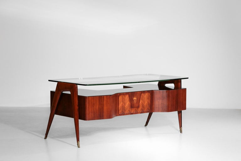 Incredible desk by the famous designer Vittorio Dassi. This desk has a thick glass on the top supported by a structure in walnut. Another glass in brown is situated on the top of the cases. Nice marquetry and brass legs. Many details and curb,