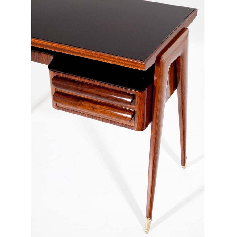 1950s Italian desk by Vittorio Dassi on elegant legs with brass sabots, two drawers to the right and a writing surface with glass top.