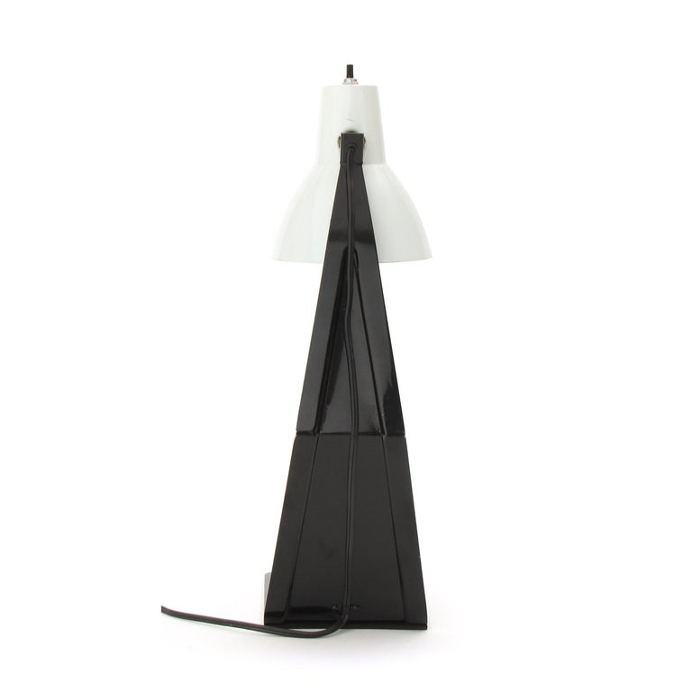 A desk / table lamp made of a singular stamped, die cut and folded piece of metal, painted black with a pivoting shade.