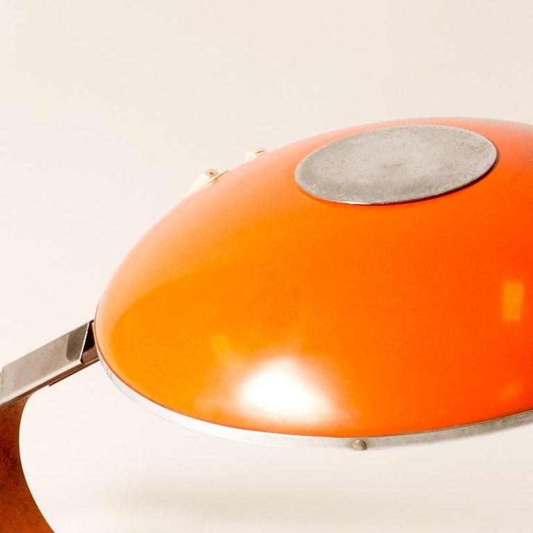 An orange metal Mid-Century desk lamp.