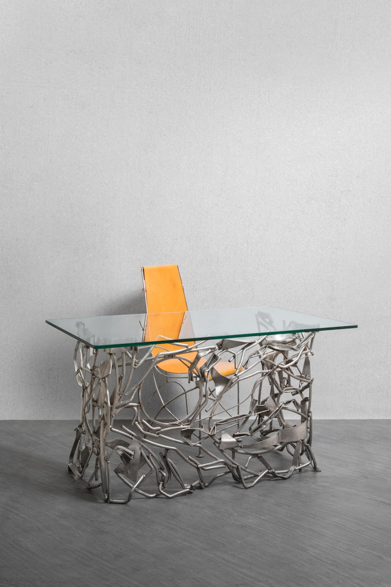 Little desk or console, composed of folded and entangled metal tubes. Rectangular glass slab.