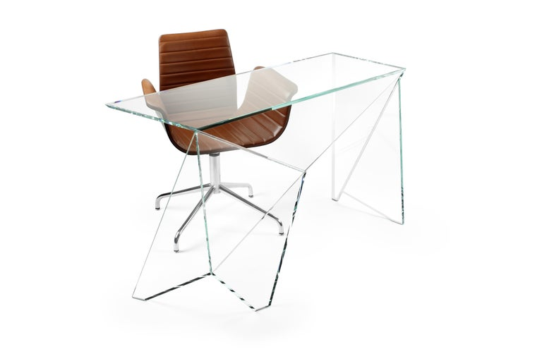 The slim desk 'Origami' is made of crystal glass. Desk dimension: L 120 W 50 H 75 cm. The inspiration for origami came from the observation of a simple piece of paper which, being folded a few times according to an antique Japanese technique,