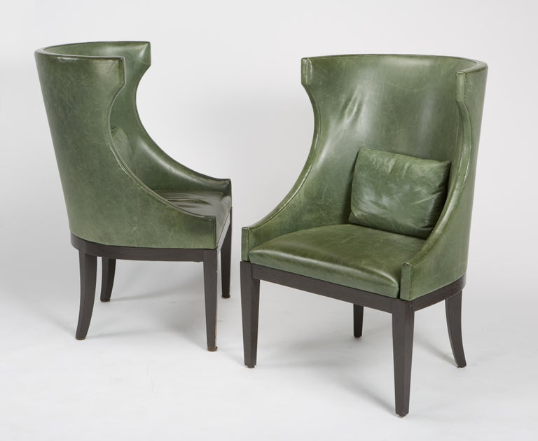 Finely crafted pair of high wing back club chairs by Dessin Fournir with classical modern form, having distressed leather from Garrett Leather with back cushions on ebony stained frame and legs, circa 2004. Leather shows wear and age. Legs may have