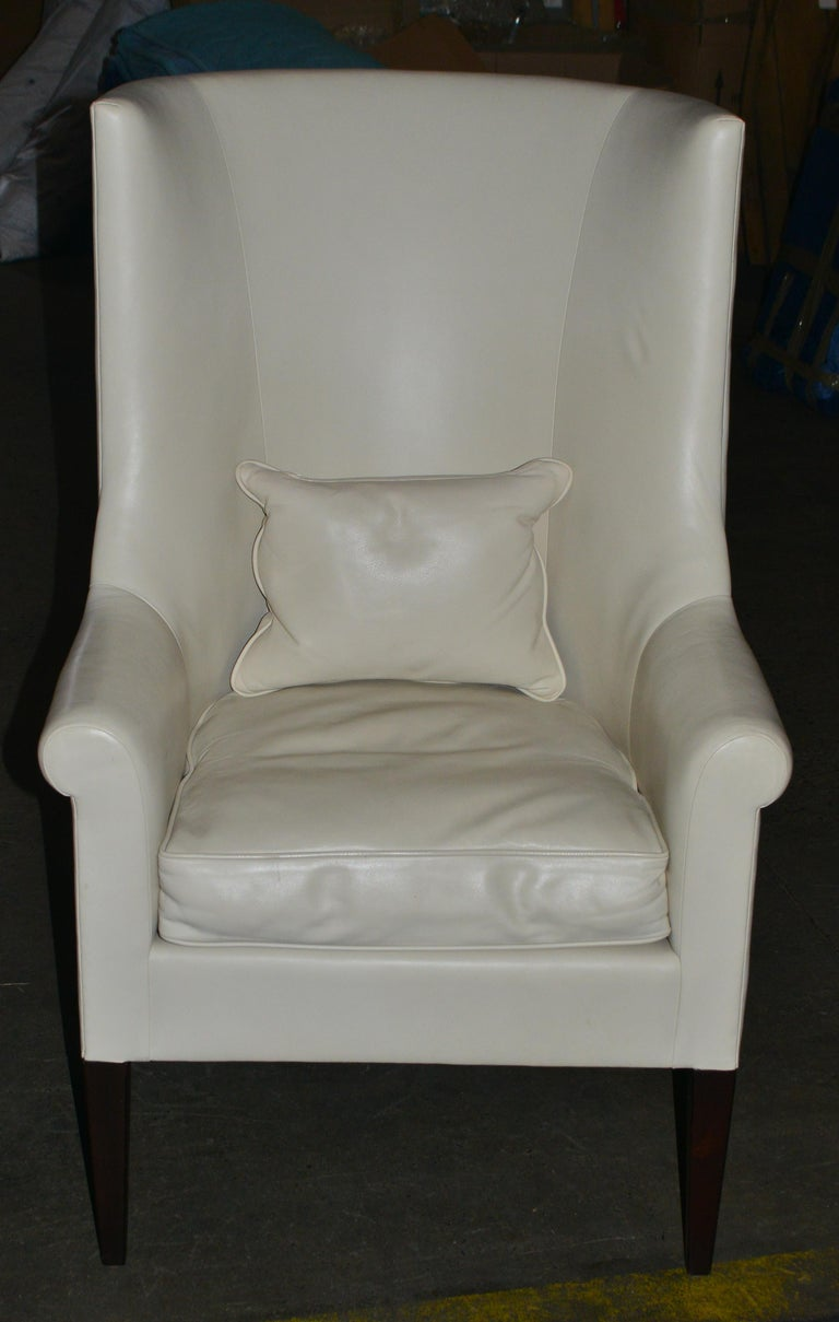 Modern pair of high back armchairs upholstered in white leather, with a pair of leather cushions, made by Dessin Fournir. Makers label located on the bottom. The pair is in great vintage condition with age-appropriate wear.