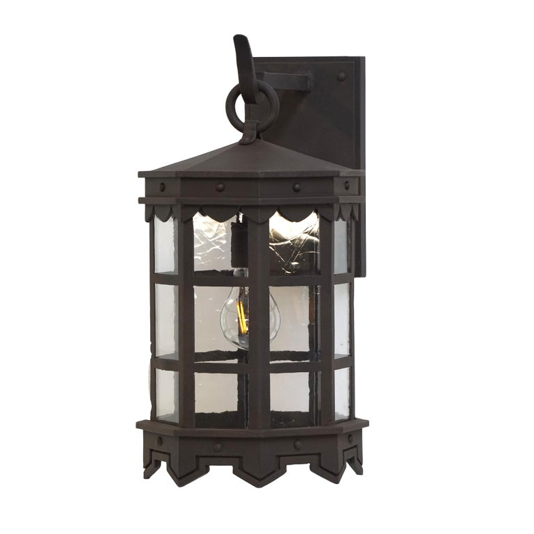 Our De La Guerra lantern finished in our premium dark zinc finish has Mediterranean style precedence with historic profiles and contemporized geometric lines. A striking fixture during the day but even more so at night when the patterned hem casts