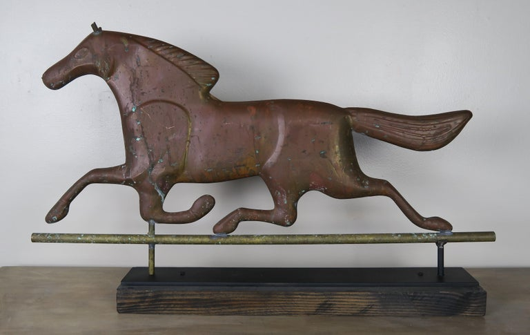 Dexter horse weathervane mounted on iron base. The copper horse was originally done in gold leaf but has weathered over the years given the piece a beautiful patina.