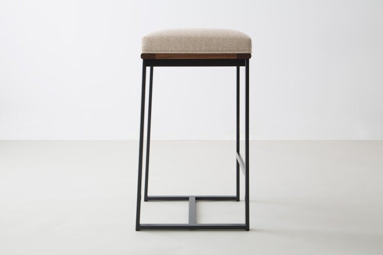The DGD counter stool finds formality and comfort in the industrial and organic.   Seat frame shown in walnut and available ash, cherry, maple, or white oak  Powder coated steel frame shown in black/grey and available in any standard RAL colors.