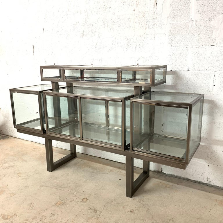 Postmodern display cabinet or vitrine. Composed of 6 compartments, 3 lower and 3 raised, each with glass doors for access. Rendered in brushed steel, polished chrome and glass by DIA, Design Institute of America, 1980s.  Dimensions: 18