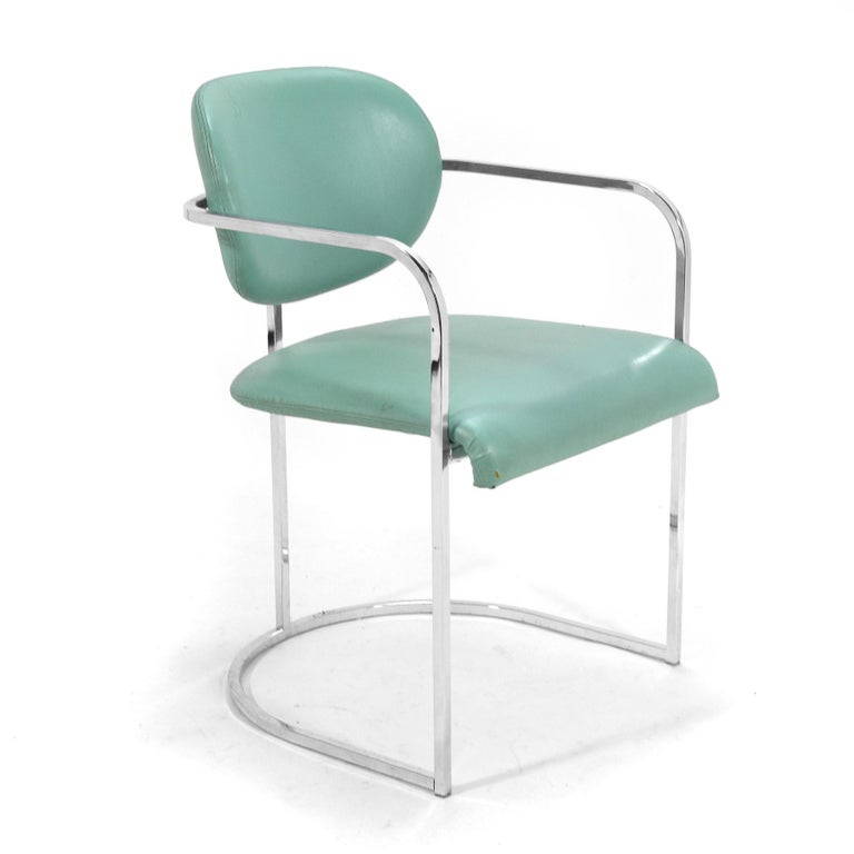 This set of armchairs by the Design Institute America have frames of chrome-plated steel which support upholstered seats and backs, giving them a floating appearance. They currently retain their original turquoise upholstery, but are ready for