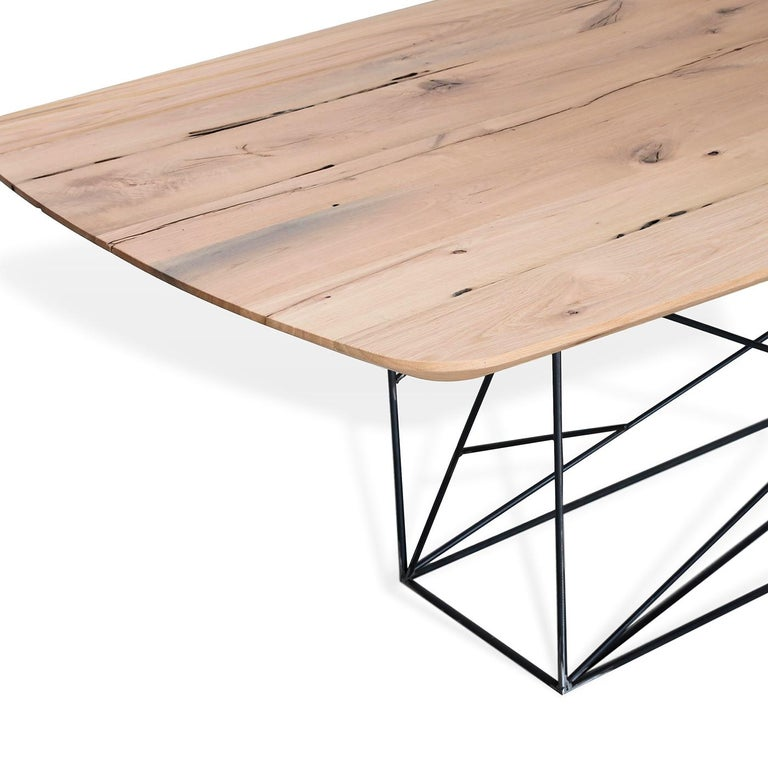 The table, with its iron base, creates a geometric weave and supports a top in solid wood with rounded corners. The construction material is Briccola oak that comes from the posts of the Venetian lagoon. The high quality wood is recovered and