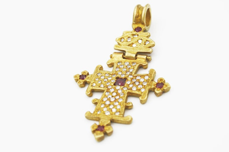 This eye catching Renato Cipullo 18k yellow gold cross pendant features 69 .70ct diamonds and 4 .32ct rubies with a delicate hinge allowing the cross and loop to flex.