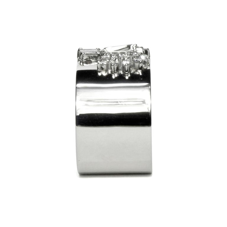 This luxurious wide-band platinum ring features deconstructed elements from repurposed vintage high jewelry stone settings in the center. These rare and classic settings were made by highly skilled craftsmen and include tapered and brilliant cut