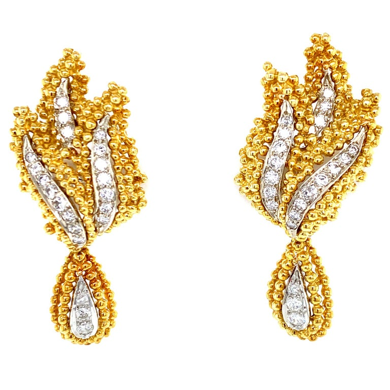 These fabulous drop leaf earrings are fashioned in 18 karat white and yellow gold. The earrings feature sparking round brilliant cut diamonds graded F-G color and VS clarity (1.00CTW). The earrings measure 2.00 inches in length,  .75 inches in