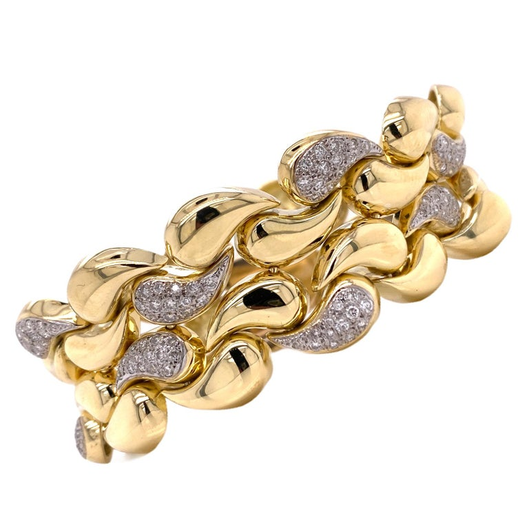 Stunning wide diamond bracelet crafted in solid 18 karat yellow gold. The infinity bracelet features 224 round brilliant cut diamonds weighing approximately 3.50 carat total weight and graded G-I  color and VS clarity. The bracelet measurs 1.0 inch