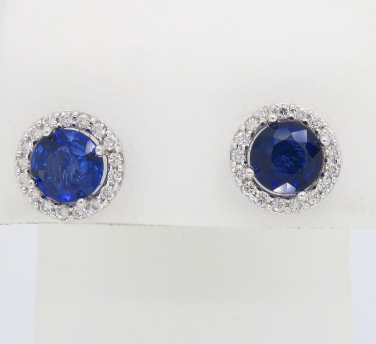 These halo style earrings feature two beautiful Blue Sapphires surrounded by approximately .50CTW of Round Brilliant Cut Diamonds.  Gemstone: Diamond & Sapphire Gemstone Carat Weight: 6.33mm Round Cut Blue Sapphire Diamond Carat Weight: