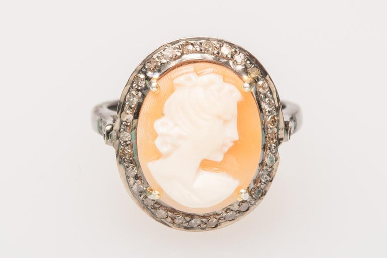 A lovely modern cameo ring set in sterling silver.  The hand-carved shell depicts the profile of a woman with intricate detail facing to the right with a nice translucence when held up to the light.  It is bordered with round, brilliant cut diamonds