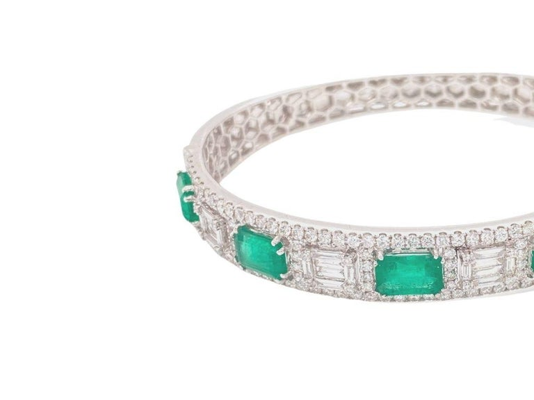 Bangle bracelet made with real/natural diamonds and emeralds. Emerald Total Weight: 4.75 carats. Diamond Total Weight: 2.95 carats. Diamond Color: G-H. Diamond Clarity: VS. Diamond Cut: Baguette and brilliant cut diamonds. Mounted on 18 karat white