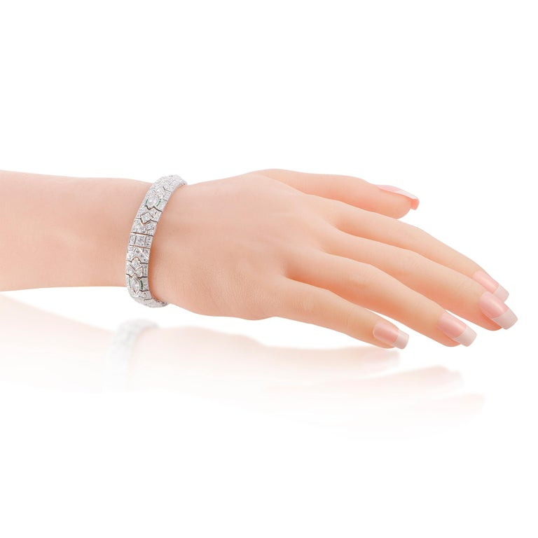 """This LB Exclusive bracelet is crafted from platinum and set with diamonds and emeralds. The emeralds amount to 1.50 carats and the diamonds total approximately 8.25 carats. The bracelet weighs 38.1 grams and measures 7.50"""" in length.  Offered in"""