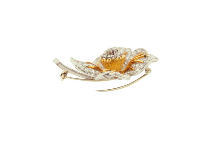Beautifully crafted diamond flower brooch set in Platinum and 18 Karat Yellow Gold.  152 Round Diamond weighing approximately 6.50 carats.  6 Baguette-cut diamonds weighing approximately 0.40 carats.  The total weight is approximately 6.90