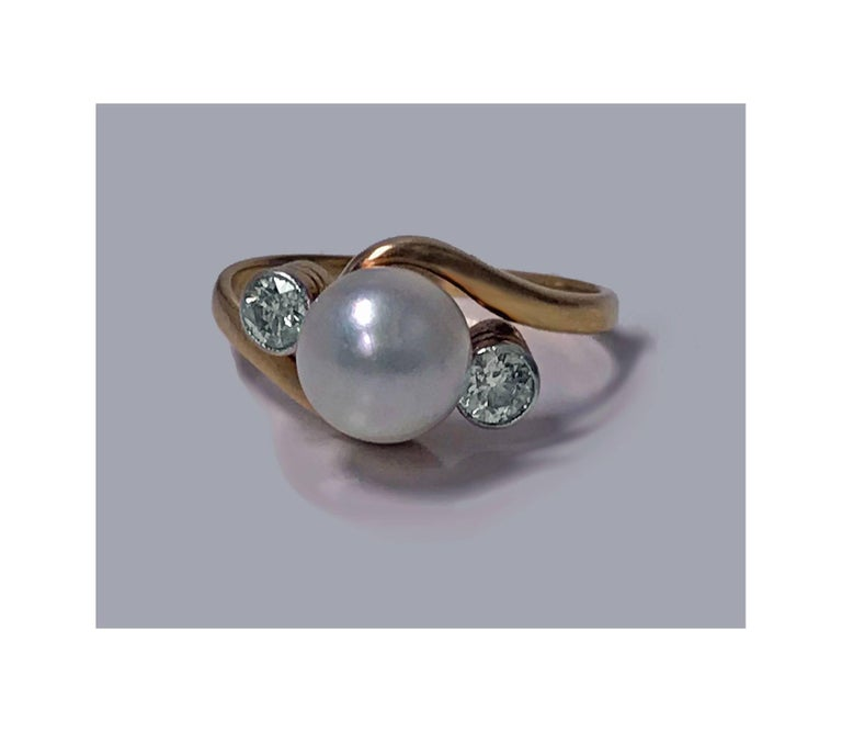 Early 20th century Diamond and Pearl 18K Ring, C.1920. The ring of twist design set with an 8.00mm fine round silver white pearl, slight rose overtone, medium nacre, good lustre, very slightly blemished, flanked on either side with a bezel