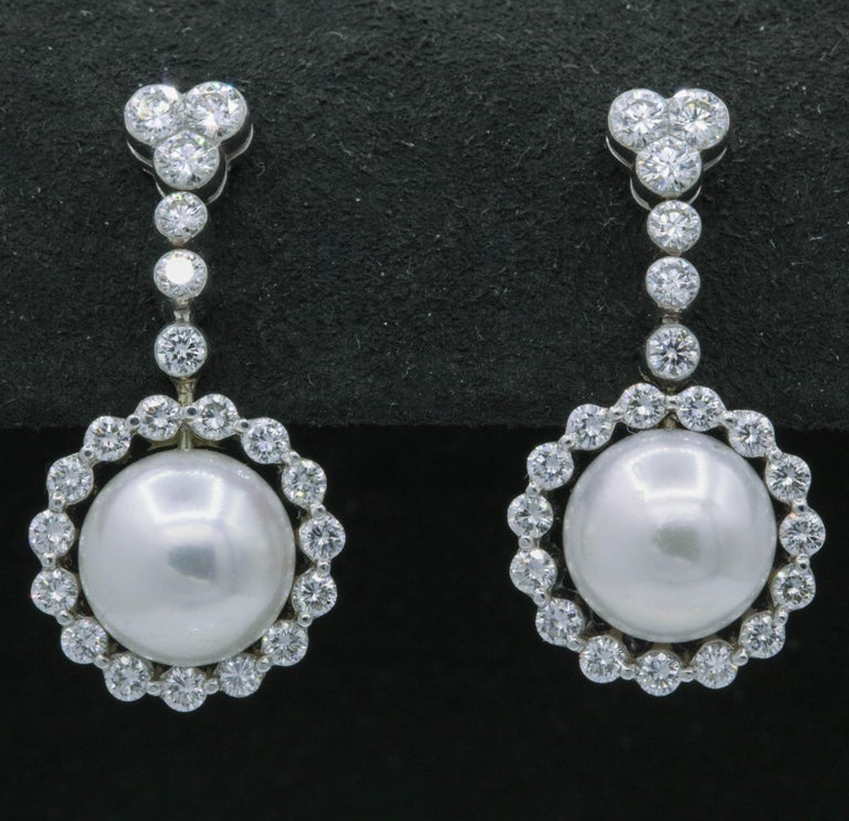 These elegant earrings features two pearls, 9.5 mm, surrounded by 42 round brilliants weighing 1.55 carats, in 18k white gold.   Color: G-H Clarity: SI