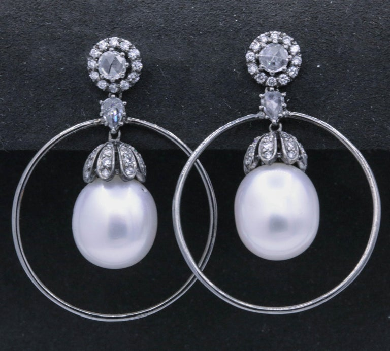 One pair of diamond and pearl hoop earrings featuring 66 round brilliants 1.58 carats, in a 18k black rhodium finish.  Color: G-H Clarity: SI