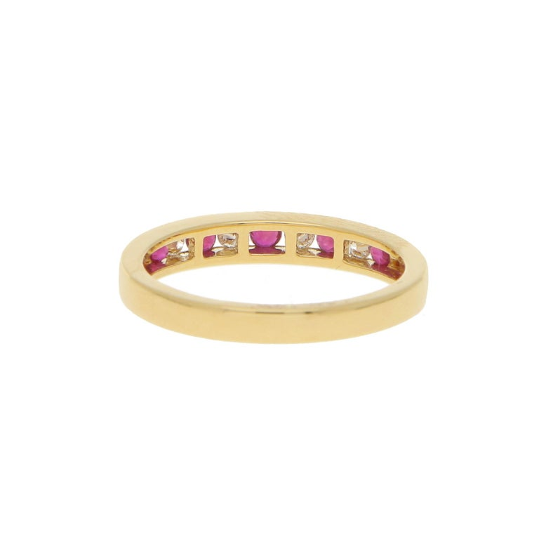 A beautiful diamond and ruby half eternity ring set in 18k yellow gold. The ring is composed of 9 round brilliant cut stones altogether, 5 of which being rubies and 4 diamonds. All the stones are perfectly set within a 2mm yellow gold band.  The
