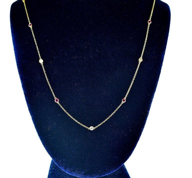 Ruby and diamond long gold chain, 30 inches in length, weighing 5.85 grams.  There are 6 round brilliant cut diamonds all H color and VS in clarity.  The total diamond weight is .50 cts., there are 9 fine red natural rubies all matching well in