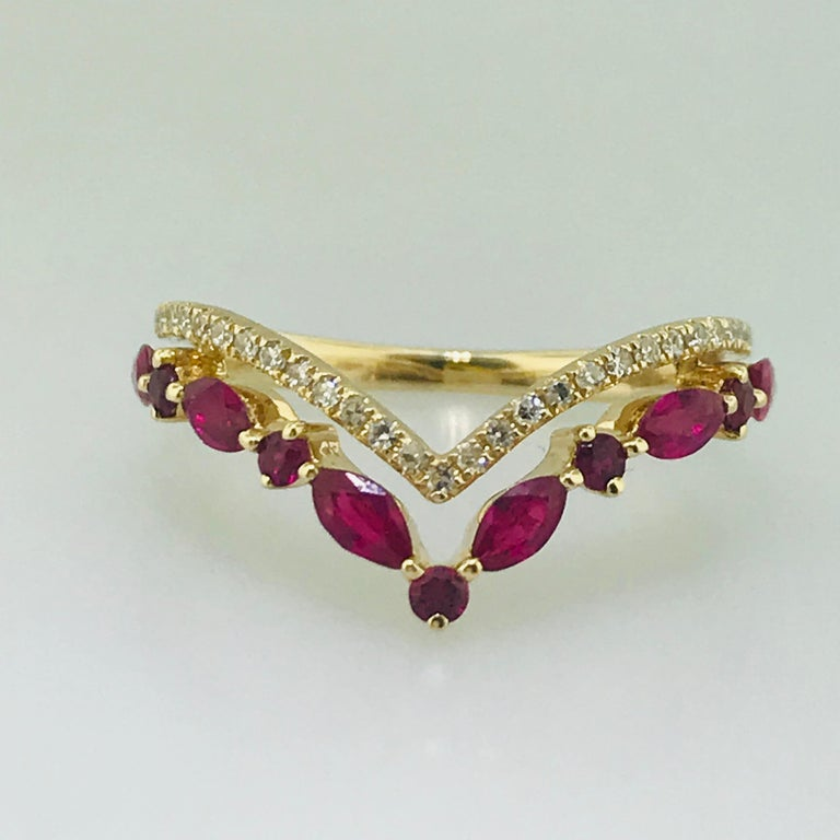 Modern V Band Meet the diamond and ruby V band. This 14 karat yellow gold v band has such a fun personality! With a round brilliant diamond v design on top of an alternating round and marquise shaped genuine ruby v band, meeting at the back and