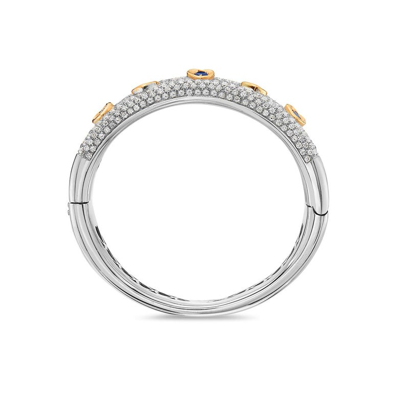 This statement bangle features 8.76 carats of diamonds and 1.15 carats of sapphire set in 18K white and yellow gold. Diameter is 2 1/4 inches. 72 grams total weight. Made in  Italy.