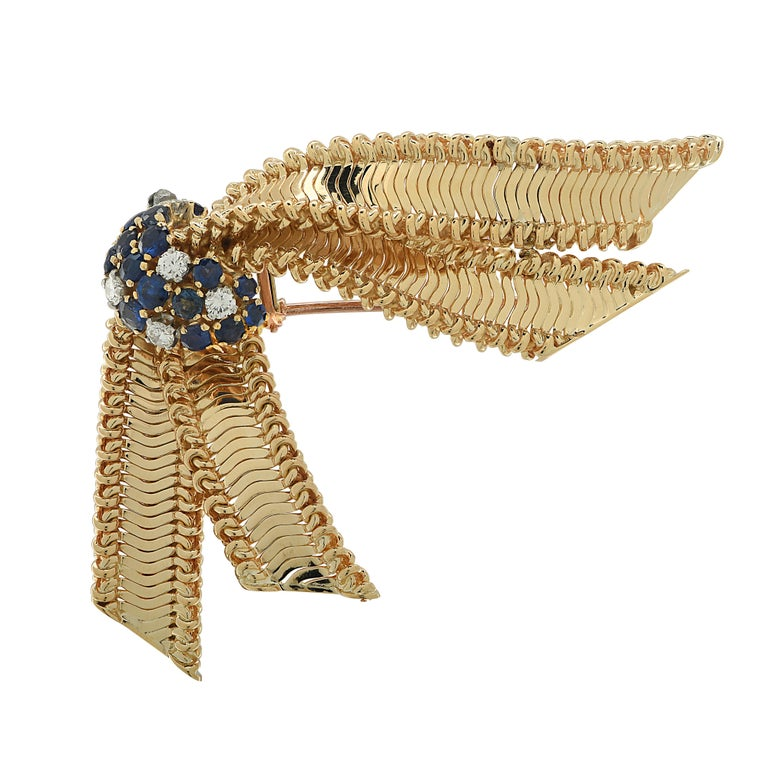 Enchanting brooch pin crafted in 18 karat yellow gold, featuring 6 round brilliant cut diamonds weighing approximately .50 carats total, G color, VS-SI clarity and 17 round blue sapphires weighing approximately 1 carat total. This delightful brooch