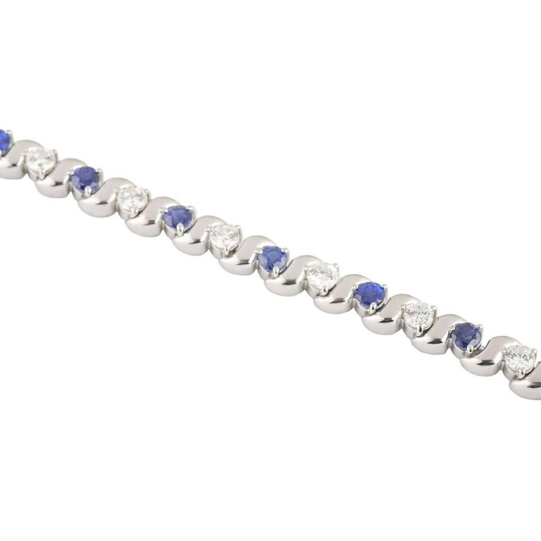 A beautiful 18k white gold diamond and sapphire bracelet. The bracelet comprises of round brilliant cut diamonds alternating in a wave design with round brilliant cut sapphires. The diamonds have a total weight of approximately 1.95ct, G colour and
