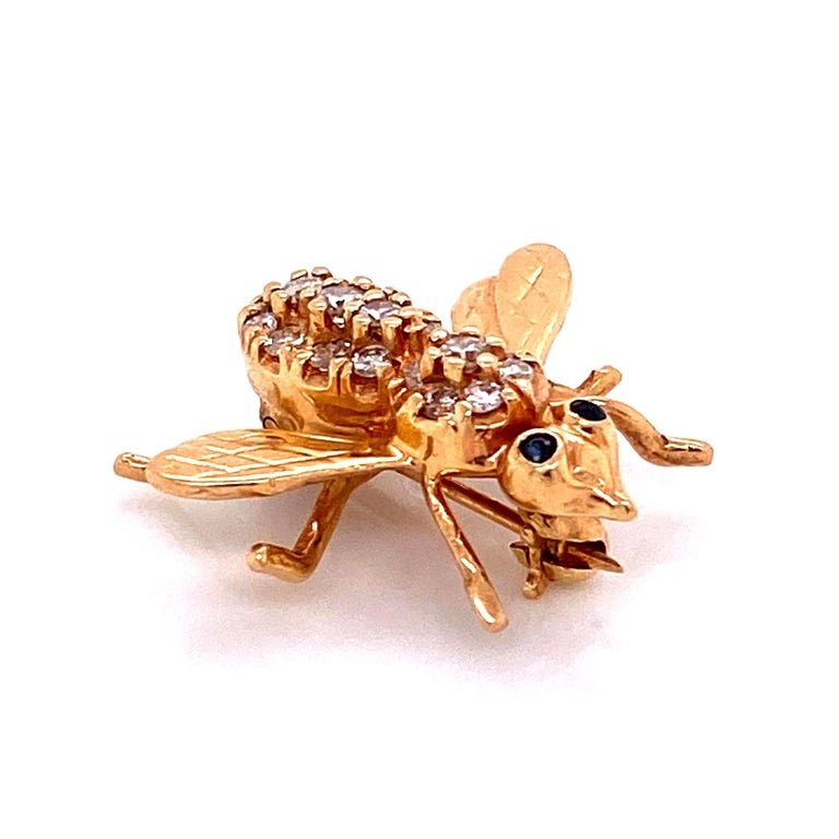 Simply Beautiful, Stylish and finely detailed Diamond Bee with Sapphire Eyes Brooch Pin hand pave set with Diamonds, weighing approx. 0.26 Carats on its back and dark vivid blue Sapphire eyes. Hand crafted in 14 Karat yellow Gold. The Pin is in