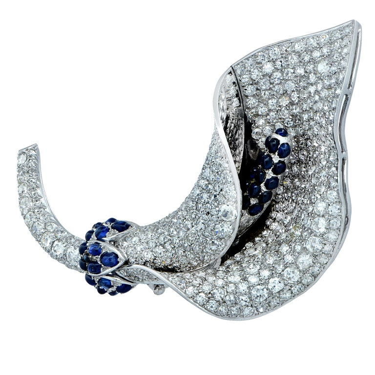 Sensational Art Deco brooch crafted in platinum, showcasing European cut and single cut diamonds weighing approximately 12 carats, G-J color, VS-SI clarity, accented by approximately 1.5cts of cabochon blue sapphires, finely crafted in a Lily. This