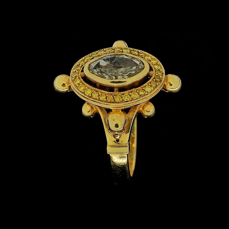 This 18kt yellow gold ring with diamonds and skulls is dark opulence at it's finest.   This high fashion gothic statement ring is handmade in 18kt yellow gold, featuring a central bezel set oval cut diamond, 1.02ct in weight, (8.91mm x 5.68mm) SI in