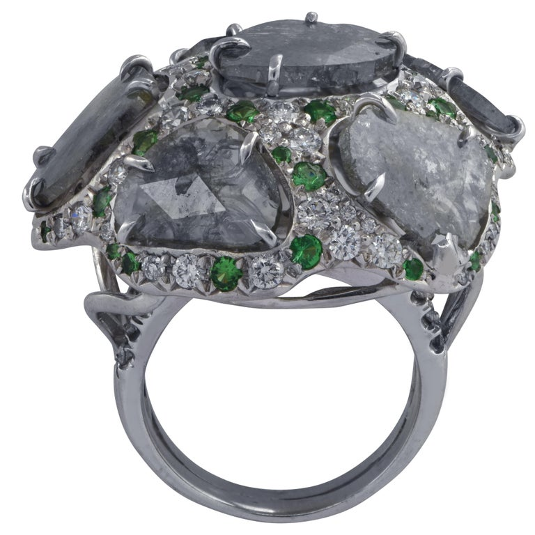 Striking domed ring crafted in 18k white gold featuring 5 diamond slices weighing approximately 10 carats total, accented by 80 round brilliant cut diamonds weighing approximately 1.30 carats total, G color VS clarity and 30 Tsavorite Garnets