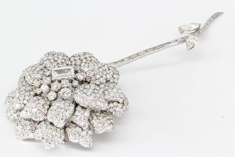 Impressive diamond and 18K white gold flower brooch with separating stem. It features approx. 40cts of high grade round brilliant cut diamonds, with approx 2.5cts emerald cut diamond as the center stone. The stem has baguette cut and marquise cut