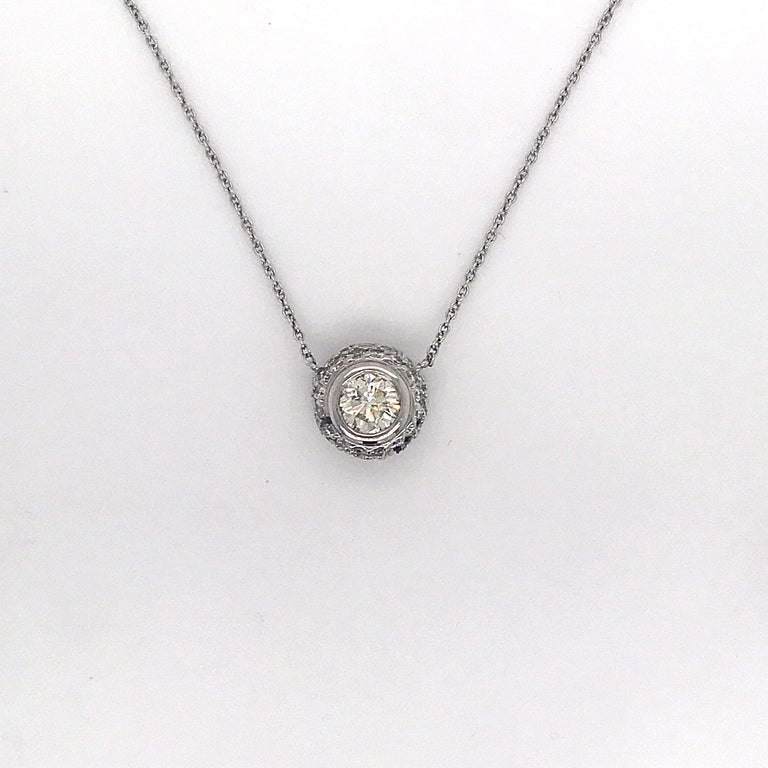 Diamond pendant necklace featuring one round brilliant flanked with numerous diamonds weighing 1.36 carats, in 14k white gold.  Color: J Clarity: SI1