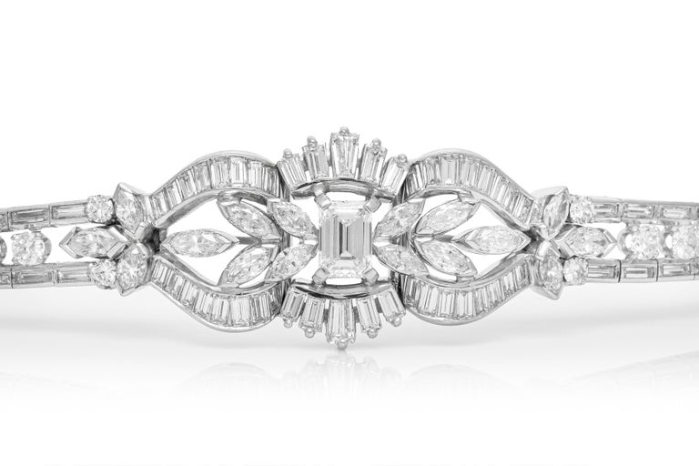 Bracelet, finely crafted in platinum with an emerald cut diamond center stone weighing approximately a total of 1.50 carat and additional diamonds weighing approximately a total of 12.00 carat. Circa 1950's.