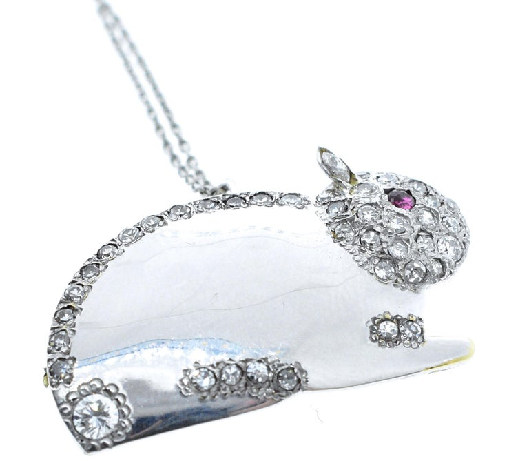 Diamonds set in 18K white gold in the motif of a bunny with a natural ruby eye. He has 40 white brilliant cut diamonds throughout his body with a total diamond weight of .75 cts. In fine condition, he is 1.5 inches in length and can be worn as a